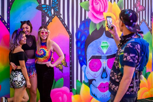 Girls posing in front of the art at Day of the Dead