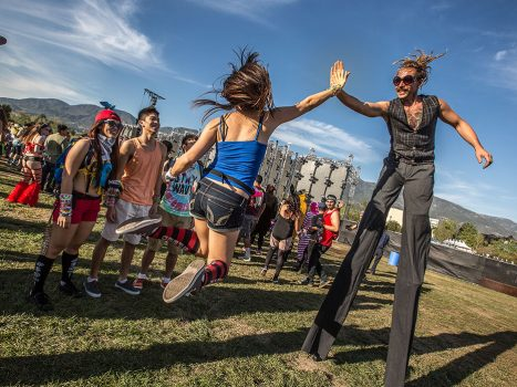 A stilt-walker high-fives a Headliner at Beyond Wonderland SoCal 2015
