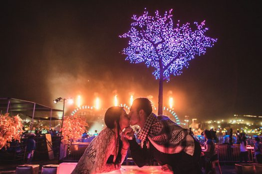 Two Headliners kiss at a SkyDeck table at Beyond Wonderland SoCal 2015
