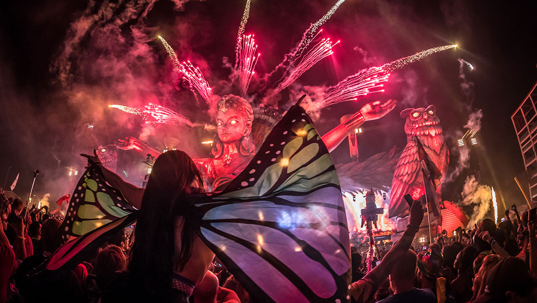 A Headliner with butterfly wings watches the show at kineticFIELD