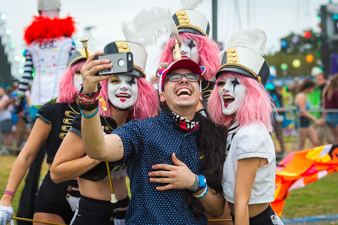 Costumed performers pose for a selfie with a happy Headliner