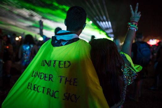 "A Headliner in a cape that says, ""United Under the Electric Sky"""