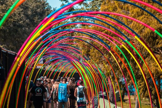 Headliners walk under a colorful archway