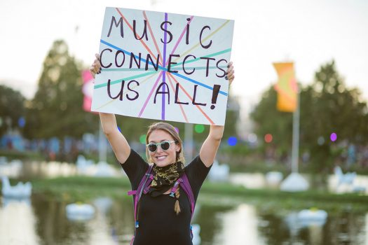 "A woman with a ""Music Connects Us All!"" sign"