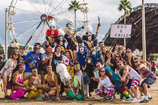 "A group of Headliners and performers with an ""EDC & Chill?"" sign"