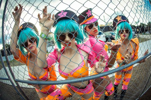 "Four costumed ""Military Brats"" leer through a fence"