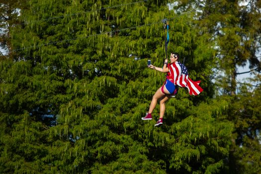 A Headliner on a zip line with an American flag