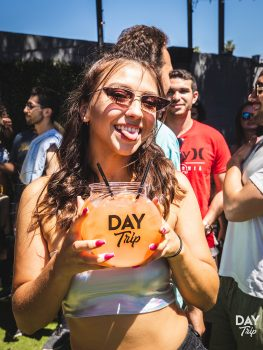 girl holding up a daytrip drink