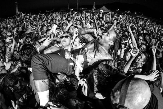 An artist crowd-surfs with a microphone