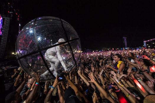 An artist crowd-surfs in a giant bubble